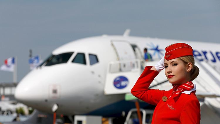 Una miembro de la tripulación de la compañía rusa Aeroflot posa delante de un Sukhoi Superjet 100