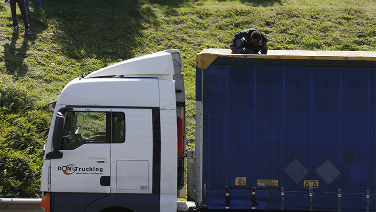 Un refugiado en la parte superior de un camión en su intento por pasar clandestinamente a Inglaterra a través del túnel del Paso de Calais, en Francia, el 22 de mayo de 2015.