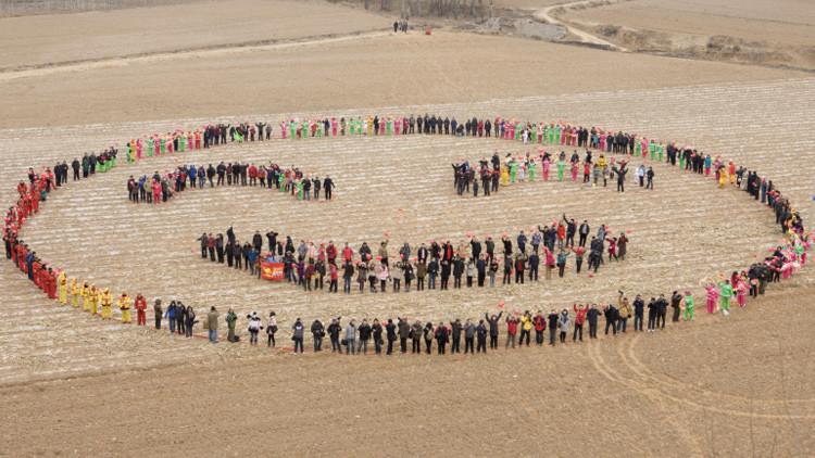 Los chinos forman una cara sonriente en un campo para celebrar el Año Nuevo