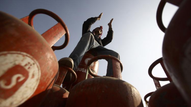 Un hombre alza las manos sobre varias bombonas de gas