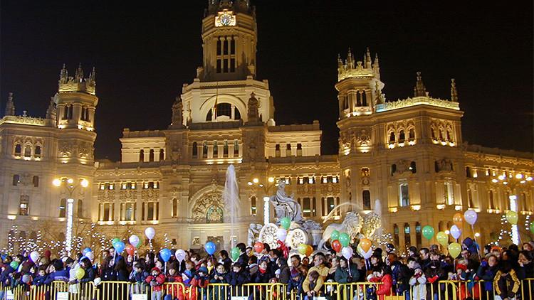 Padres esperan junto a sus hijos el tradicional desfile de la Epifanía junto a la fuente del Palacio de Cibeles, en Madrid, España.