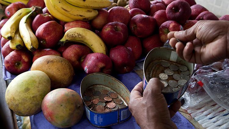 Un comerciante callejero de fruta toma el cambio de su improvisada caja registradora en San Juan, Puerto Rico