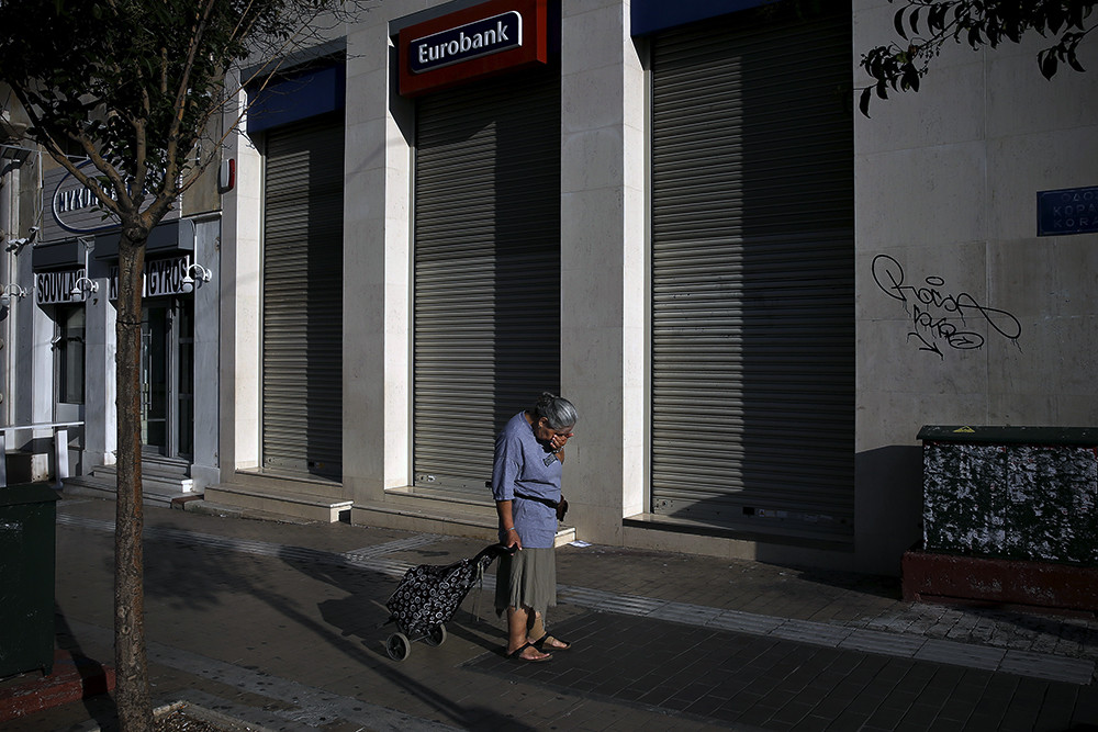 A woman pulling a shopping cart reacts outside a closed Eurobank branch in Athens, Greece June 29, 2015