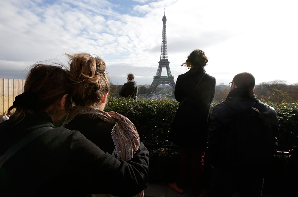 People observe a minute of silence at the Trocadero in front the Eiffel Tower to pay tribute to the victims of the series of deadly attacks on Friday in Paris, France, November 16, 2015.
