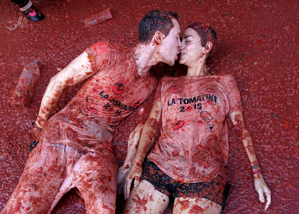 """Revelers kiss each other while lying in tomato pulp after the annual """"Tomatina"""" (tomato fight) in Bunol, near Valencia, Spain, August 26, 2015"""