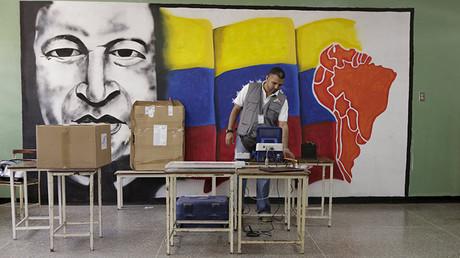 Trabajador del Consejo Nacional Electoral configura una máquina de votación frente a un muro con un dibujo de Hugo Chávez