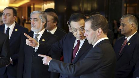 El primer ministro chino, Li Keqiang, habla con su homólogo ruso, Dmitri Medvédev en una exposición en Zhengzhou, China, el 14 de diciembre de 2015