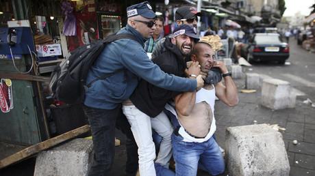 Un agente secreto israelí detiene a un manifestante palestino