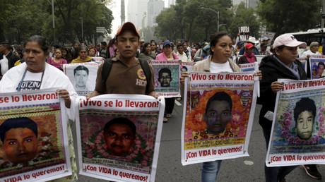 Familiares de los estudiantes desaparecidos de Ayotzinapa llevan sus fotos durante una marcha en la ciudad de México el 26 de octubre de 2015