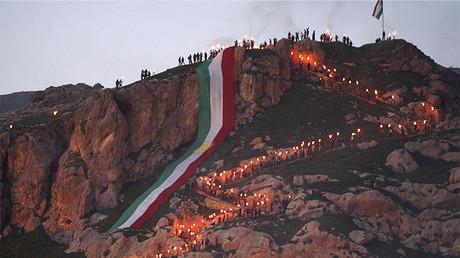 Kurdos iraquíes llevan antorchas de fuego a una montaña por cuya ladera se extiende una bandera gigante de la región del Kurdistán autónomo de Irak, cerca de Dahuk, el 20 de marzo de 2014.