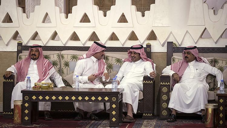 Saudíes con ropa tradicional esperan sentados durante una reunión entre el rey Salmán bin Abdulaziz de Arabia Saudita y el secretario de Estado estadounidense, John Kerry, en la ciudad de Diriyah, Arabia Saudita, el 24 de octubre de 2015.