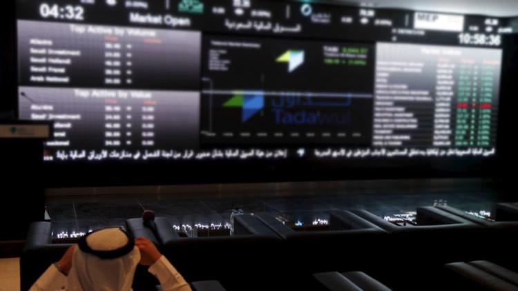 Un comerciante árabe consulta la lista de compras en la Bolsa de Riad (Tadawul)