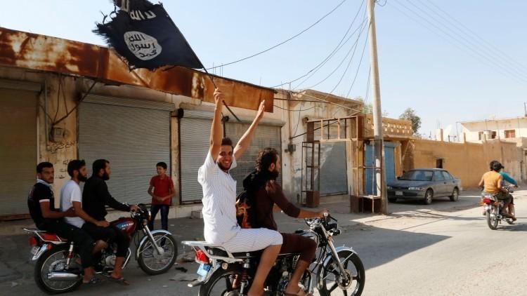 Residentes de la localidad siria de Raqa ondean la bandera del Estado Islámico