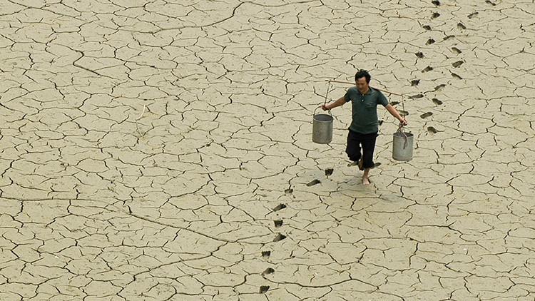 Un campesino camina sobre un estanque reseco a las afueras de Baokang, provincia de Hubei, China, el 10 de junio de 2007.