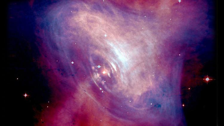 Una foto del pulsar del Cangrejo en la que se aprecian los rayos X (en azul) y la imágen con información óptica (en rojo).