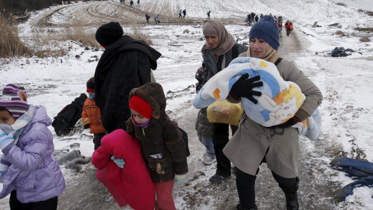 Refugiadas cruzan un campo helado cerca de la frontera con Macedonia