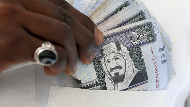 Un hombre muestra billetes de riyal saudí