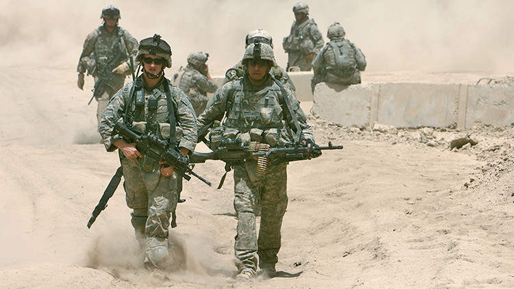 U.S. soldiers walk through dust in front of their base after a patrol in Baquba June 26, 2007. The United States must not rush to withdraw forces from Iraq's volatile Diyala province and other areas targeted in the latest American military offensive, a U.S. general said on Monday