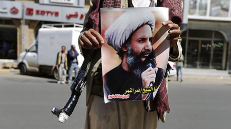 Manifestante armado chiita sujeta un poster de Nimr al-Nimr