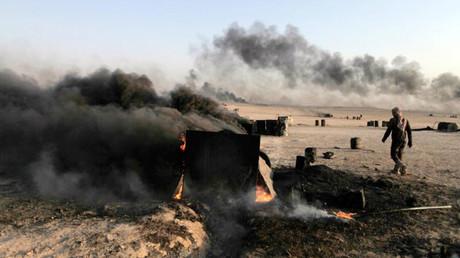 Un hombre camina por una refinería improvisada en Al Raqa, Siria