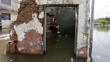 Un hombre sentado en casas parcialmente sumergidas por el agua luego de las inundaciones en Asunción, Paraguay, el 27 de diciembre de 2015.