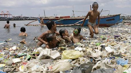 Los niños juegan mientras se bañan en la bahía de Manila