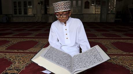 Imagen ilustrativa. Un niño lee el Corán durante el Ramadán en una mezquita en Islamabad, Pakistán, el 12 de julio de 2015.