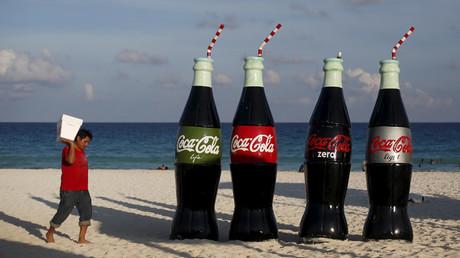 Un hombre camina al lado de unas enormes botellas de Coca-Cola en una playa de Cancún, Quintana Rico, México
