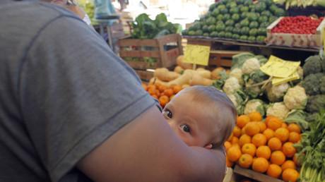Una mujer amamanta a su bebé mientras aguarda para comprar frutas y verduras en el Mercado Central, en Buenos Aires, Argentina