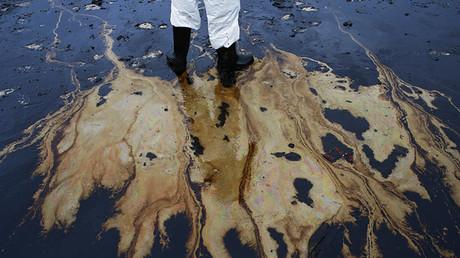 Un soldado tailandés con traje de protección participa en una operación de limpieza en la provincia de Rayong tras una fuga de petróleo de un oleoducto en el golfo de Tailandia.