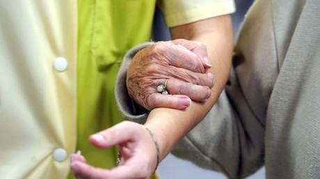 Una residente de 'La Souvenance', un centro de acogida para personas con Alzheimer, camina con la ayuda de una cuidadora, Le Mans, Francia.