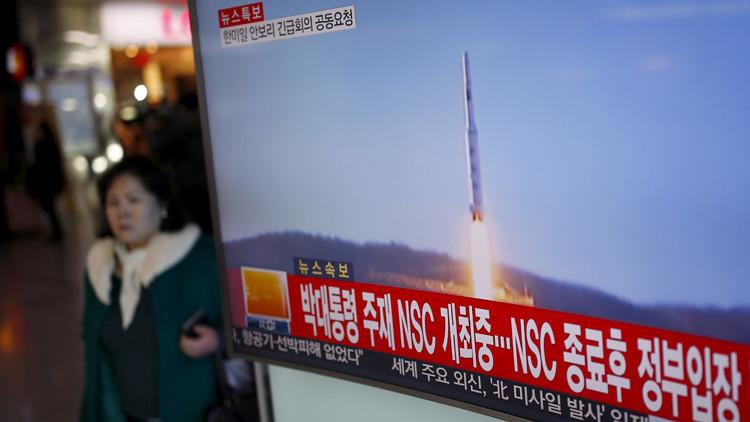 Un pasajero pasa junto a una pantalla de televisión en Seúl, Corea del Sur, que informa sobre el lanzamiento de un cohete de largo alcance realizado por Corea del Norte.