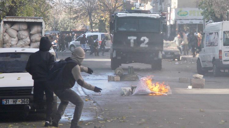 Manifestantes kurdos lanzan piedras contra un vehículo de la Policía en protesta por los ataques contra la ciudad suroriental de Diyarbakir.