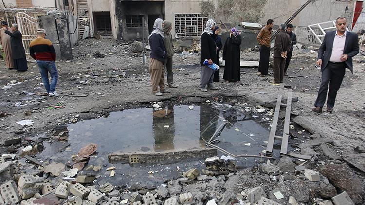 Residentes se reúnen en el lugar de la explosión de un coche bomba en Nuevo Bagdad, 12 de enero de 2016.