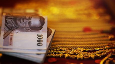 Billetes de baht al lado de oro puestos a la venta en una tienda de oro, en el barrio chino de Bangkok