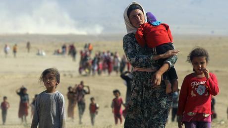 Desplazados de la minoría yazidí, perseguidos por el Estado Islámico, caminan hacia la frontera con Siria en las afueras de la montaña Sinjar, Irak.