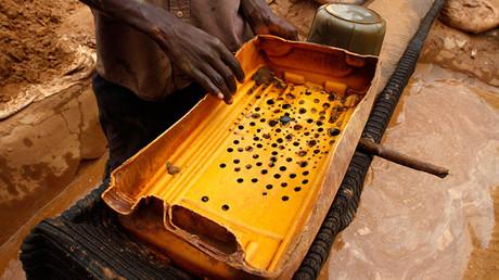 Un hombre sostiene un filtro de plástico mientras se prepara para lavar polvo de oro en una mina situada en la localidad de Bhagega, en el estado nigeriano de Zamfara, el 14 de agosto de 2013.