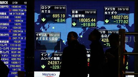 Los peatones caminan por delante de un tablero electrónico que muestra los índices bursátiles de varios países en Tokio (Japón), el 9 de febrero de 2016.