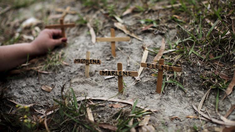 Una activista coloca cruces frente a un tribunal en San Salvador (El Salvador) con los nombres de mujeres asesinadas durante una marcha celebrada con motivo del Día Internacional de la Mujer