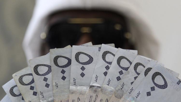 Un hombre sujeta billetes de riyal en una casa de cambio en Riad, Arabia Saudita.