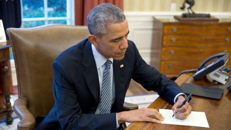 Barack Obama firmando una carta que mandó a Cuba