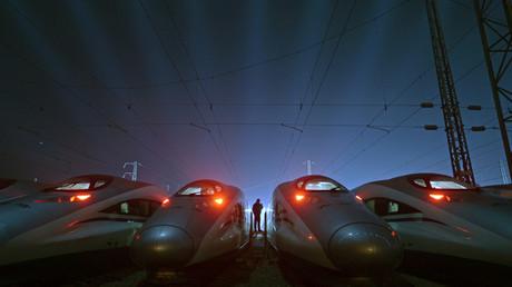 Un trabajador camina entre trenes balas de la empresa CRH (China Railway High-speed) en una base de mantenimiento de trenes de alta velocidad en Wuhan, China.