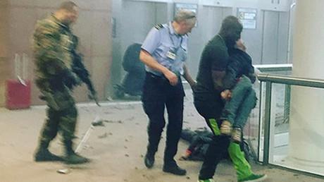 Un hombre sostiene a una persona herida tras las explosiones en el aeropuerto de Bruselas, Bélgica