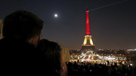 Una pareja mira la torre Eiffel iluminada con los colores de la bandera belga