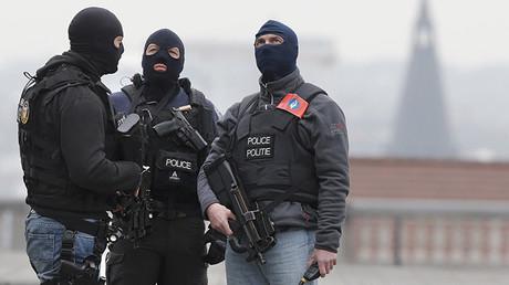 Tres policías enmascarados vigilan los alrededores del Palacio de Justicia, Bruselas, Bélgica