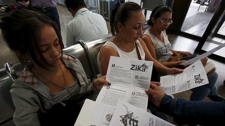 Mujeres reciben folletos informativos sobre el virus del Zika en una terminal de transporte en Colombia.