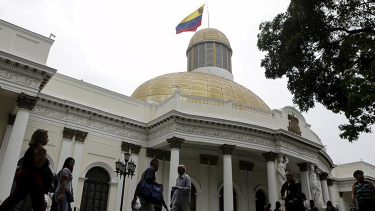 Varias personas caminan cerca del edificio de la Asamblea Nacional durante una sesión parlamentaria en Caracas, Venezuela, 5 de abril de 2016