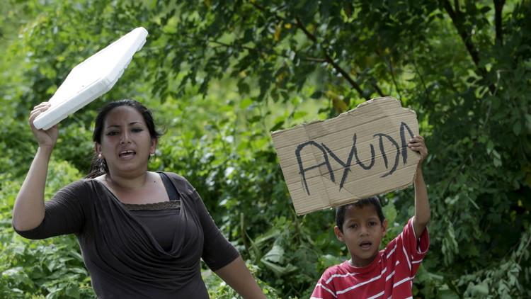 """Una mujer y un niño con un cartel que reza """"ayuda"""" tras la serie de mortíferos terremotos registrados en Ecuador, el 25 de abril de 2016."""