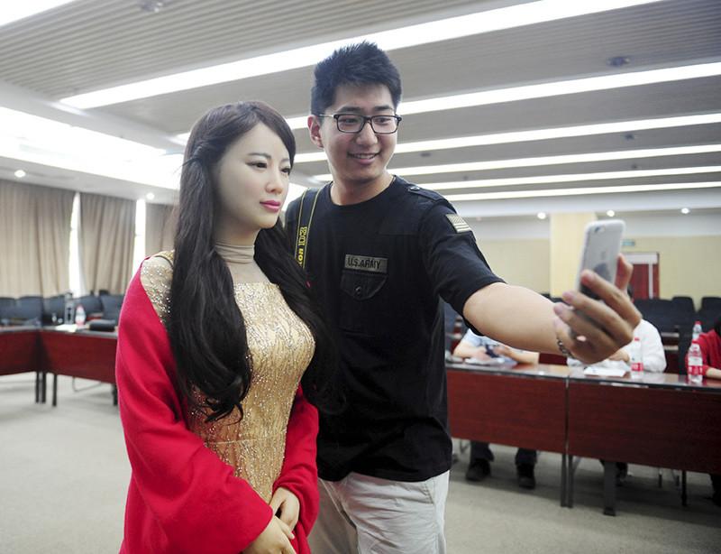 Un hombre hace un selfi con la robot Jia Jia construida en la Universidad de Ciencia y Tecnología de China, en Hefei, provincia de Anhui. 15 de abril de 2016.