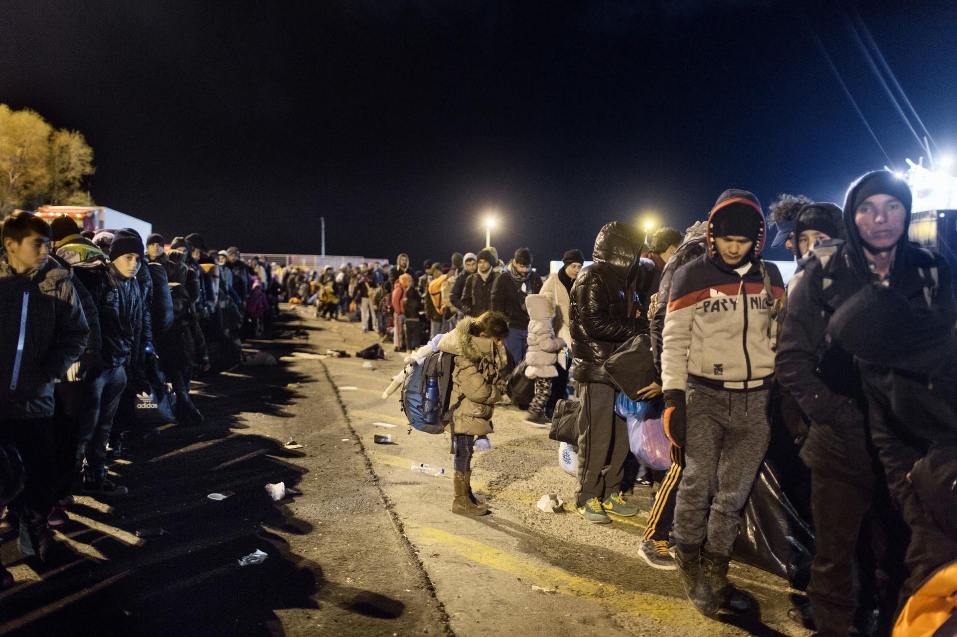 Refugiados y migrantes esperan para abordar un ferry que los lleve a Atenas en el Puerto de Mitilene en Lesbos.